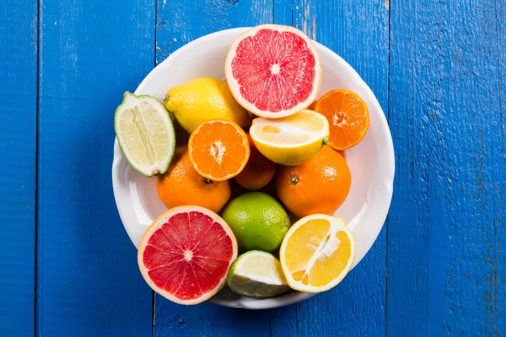 A plate of citrus fruits on a blue wooden desk.