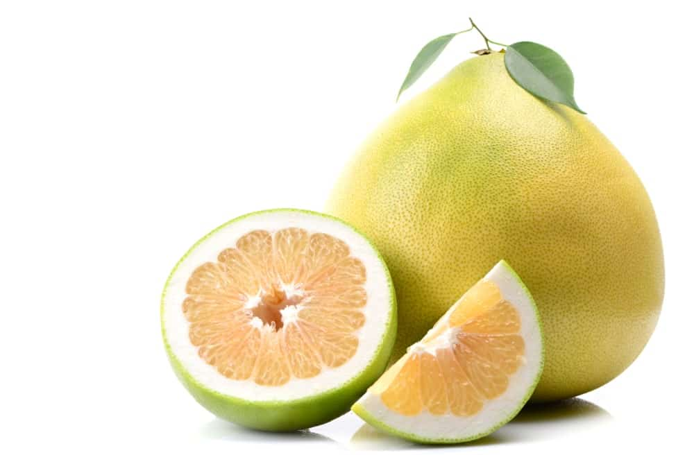 A whole Pomelo fruit and slices of pomelo.