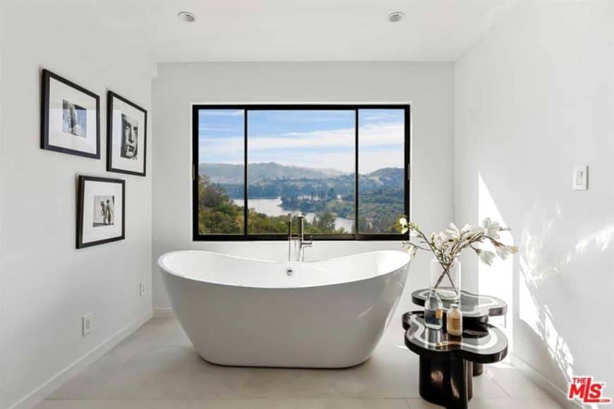 This minimalist bathroom features a freestanding bathtub with an overlooking view outside, thanks to the glass window. For a personal touch, there's an accessible black side table for plants, and some picture frames on the wall.