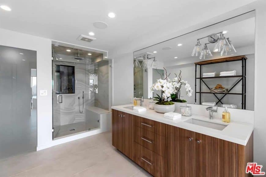 White primary bathroom featuring wooden cabinetry and walk-in shower. It also features large mirrors matches the white walls.