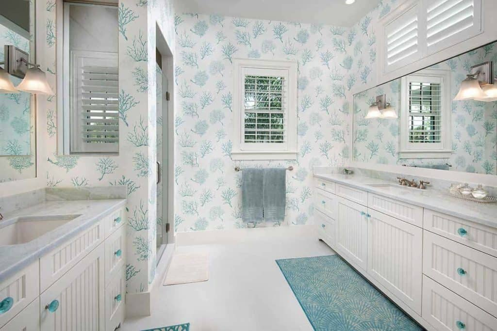 You would adore this beach-inspired bathroom with its white interior with blue accents. The white double-counters have blue handles, the wall art is painted with blue twigs while the blue rug complements the plain white flooring well. The yellow wall lamps provide great lighting for the long mirror installed above the sink.