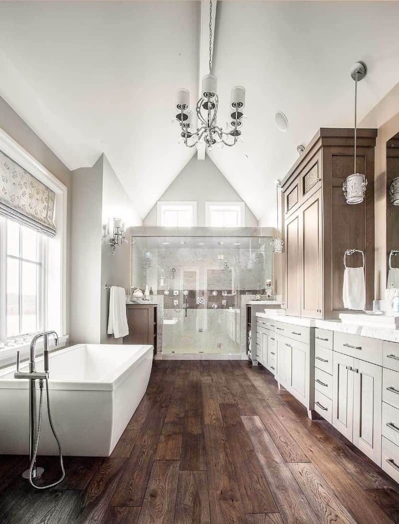 Large modern primary bathroom featuring large freestanding rectangular bathtub matches the rustic hardwood flooring. It also has wooden cabinetry and the room brightens by a chandelier.