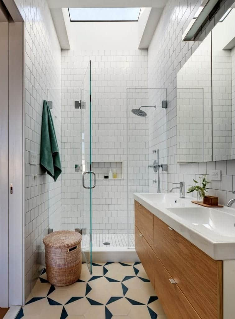 The small bathroom features wooden cabinetry and stylish carbage can. It is accompanied by a walk-in shower and a dual sink vanity against the light white marble walls.