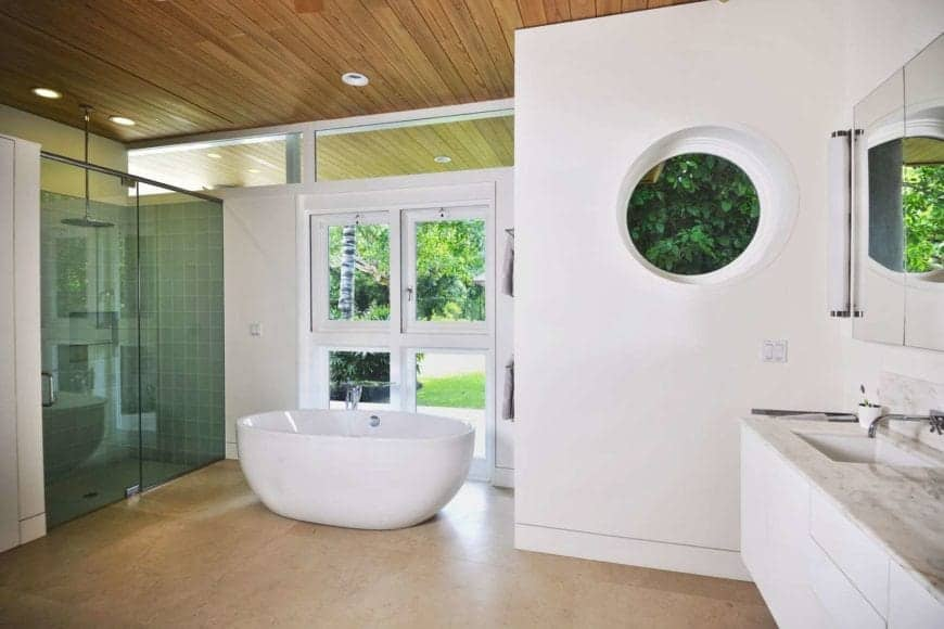 A wooden ceiling bathroom and white walls with a window with a great view outside. This room also features a single basin sink countertop match the marble flooring.