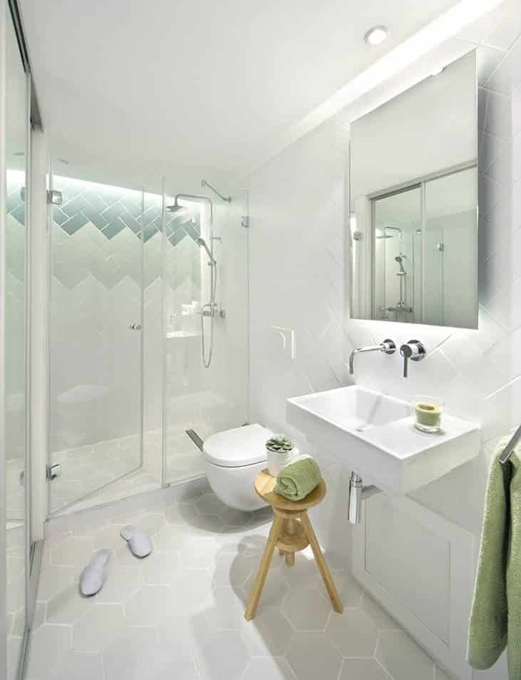 This bathroom has a nice minty feel to it with its all-white interior, balanced off with green accents. It has nice light grey hexagonal tiles that match the white floating toilet as well as the floating sink with a frameless mirror on top. The shower area has a nice medium size with lovely gradient herringbone tiles on the wall.