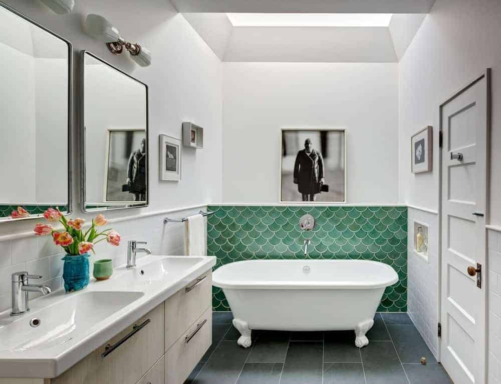 Small modern bathroom highlighting double basin sink countertop match the stylish marble flooring. This bathroom also has a stunning bathtub and a white walls with wall decors.