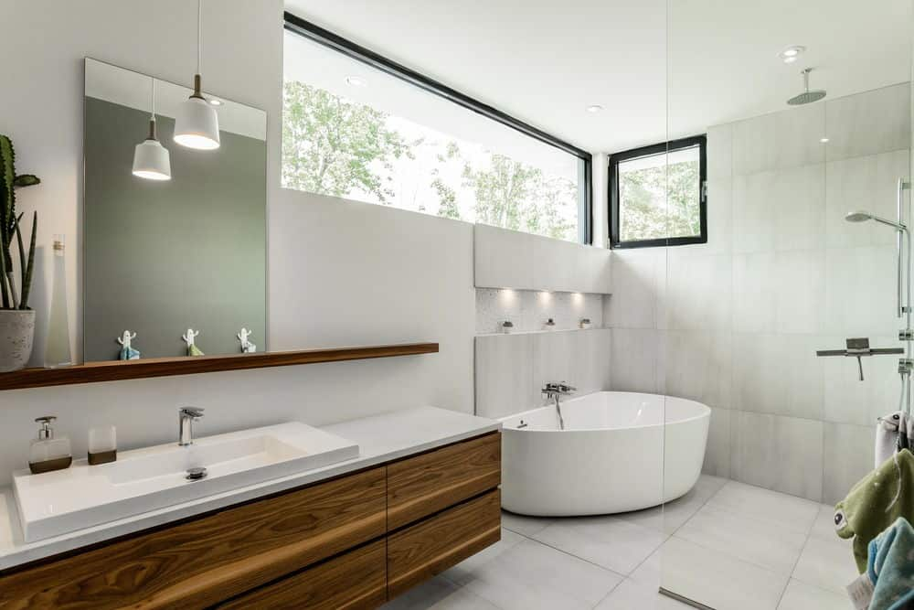 tylish bathroom with glass panel enclosed shower with bathtub. A rustic wooden vanity with a modern square basin sink brightens by hanging lights.