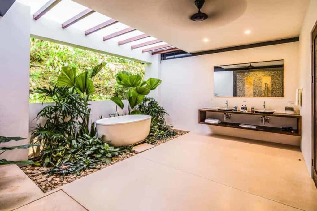 Large primary bathroom featuring freestanding bathtub and plants. This room also has wooden countertops with dual sink.
