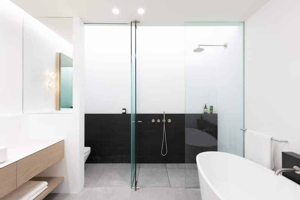 Small white bathroom with a glass panel enclosed walk-in shower and oval bathtub match the grey marble flooring. Wooden cabinetry finishes off the look.