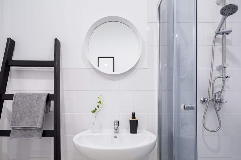 Scandinavian white bathroom with a creative ladder shelf for towels. This bathroom also has a walk-in shower and a small elegant mirror.