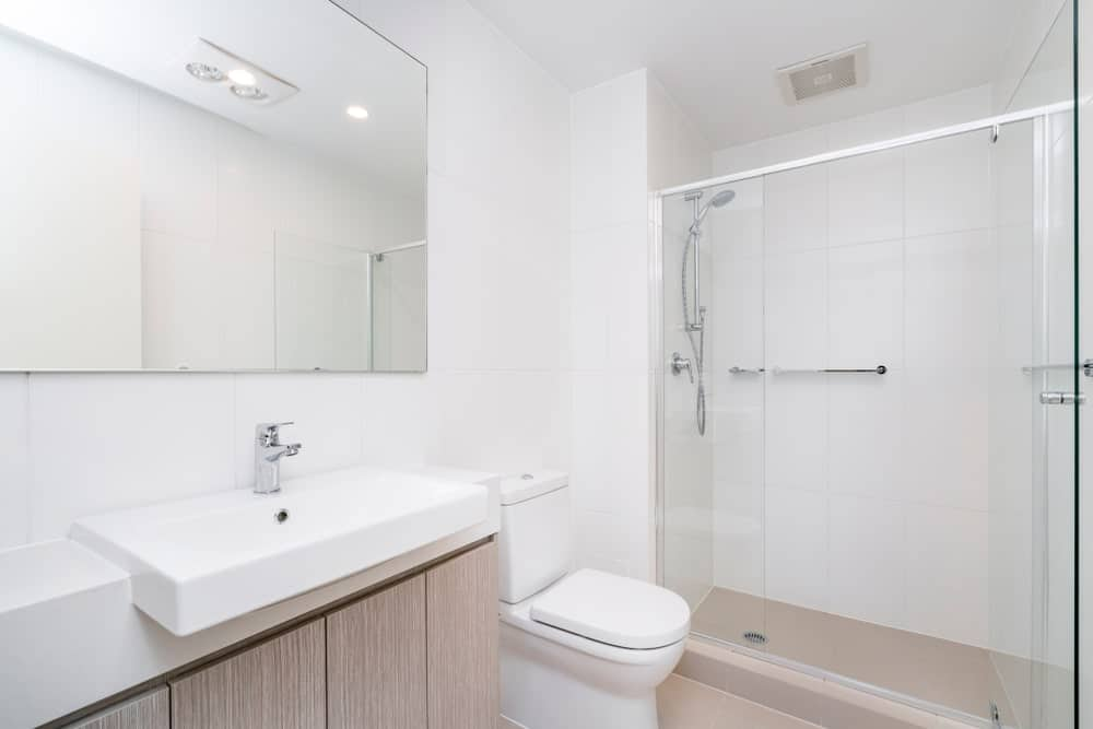 Modern minimal bathroom interior with wooden cabinets and glass shower screen. This bathroom also features traditional toilet and a large mirror on the wall.