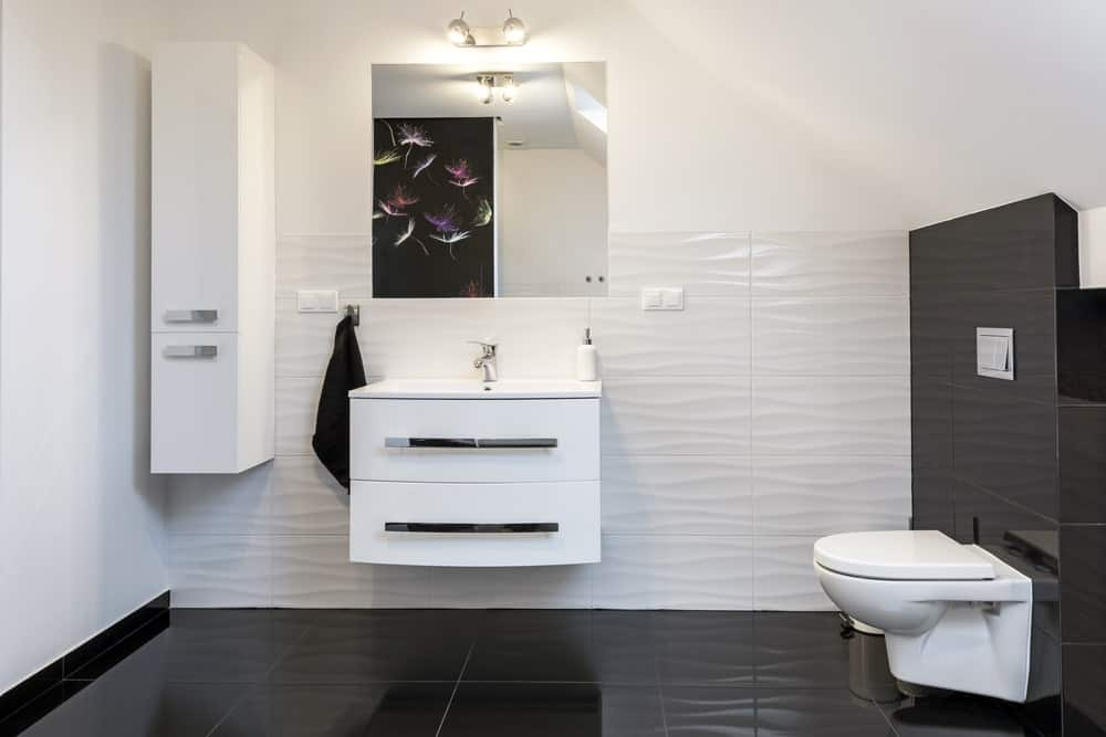 Modern design comfortable bathroom in black and white style. Modern bathroom with a wall-hung toilet and it includes a floating sink vanity that's paired with a mirror.