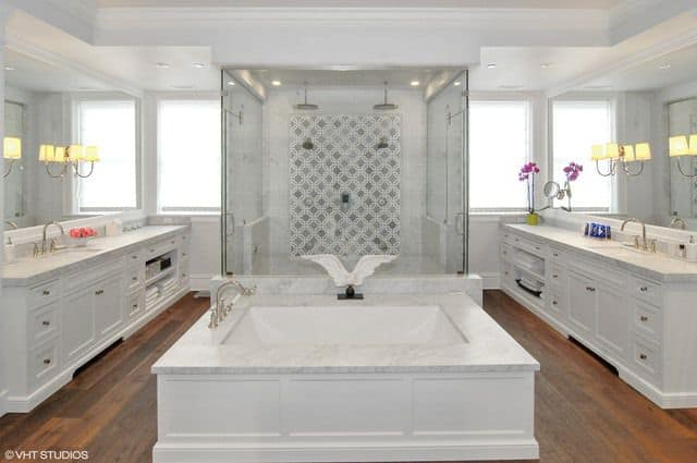 The fabulous primary bathroom showcases a white vanity paired with gorgeous large mirrors and sconces. It includes a pedestal tub on the hardwood flooring and a walk-in shower.