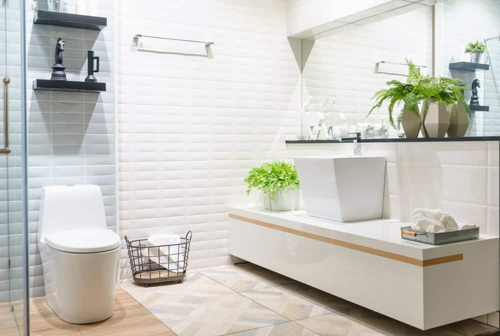 Modern spacious bathroom with bright tiles with toilet and sink. This room also features marble flooring and fashionable mirror.