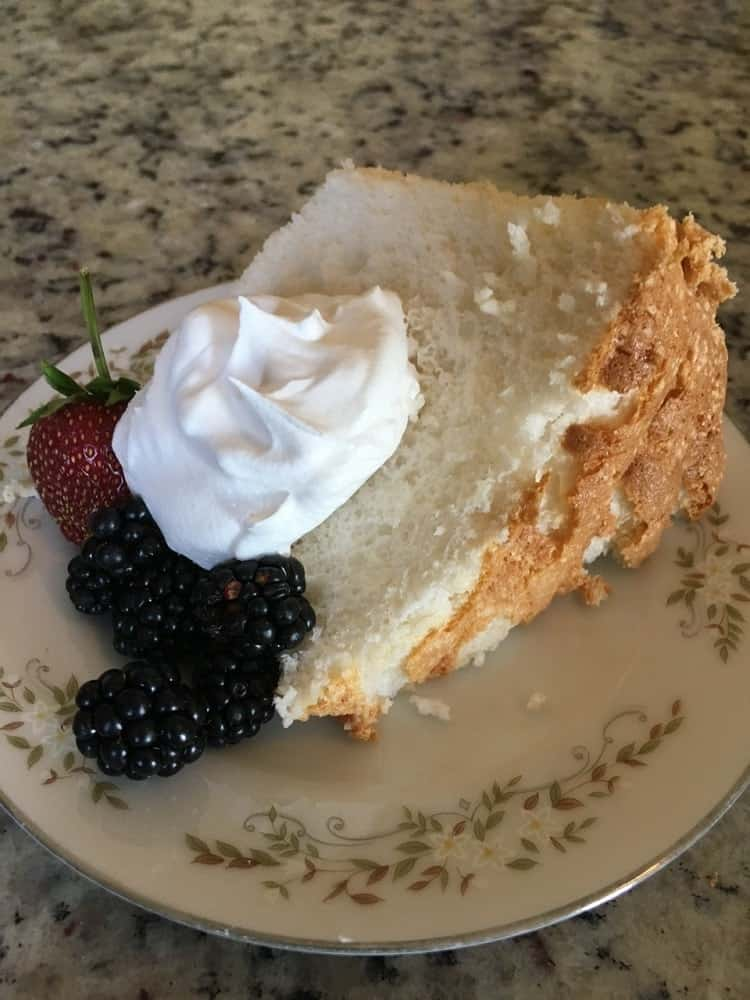 A freshly-baked slice of angel food cake with frosting and berries.