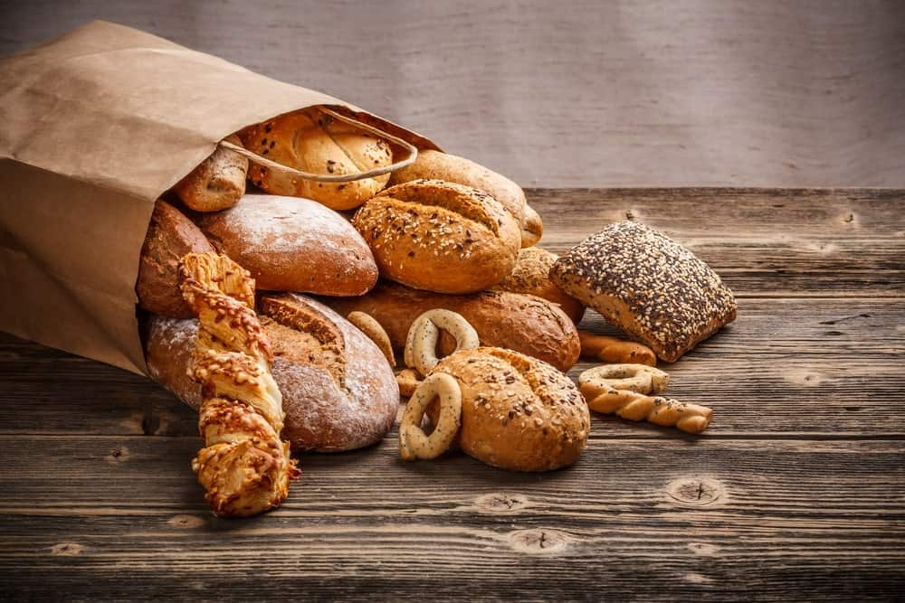 An assortment of baked goods spilling out of a paper bag.