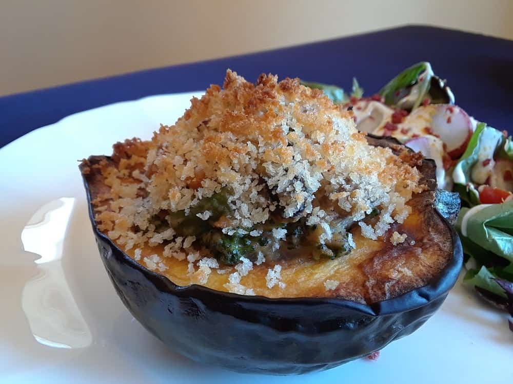 A plate of stuffed acorn squash with a side of salad.
