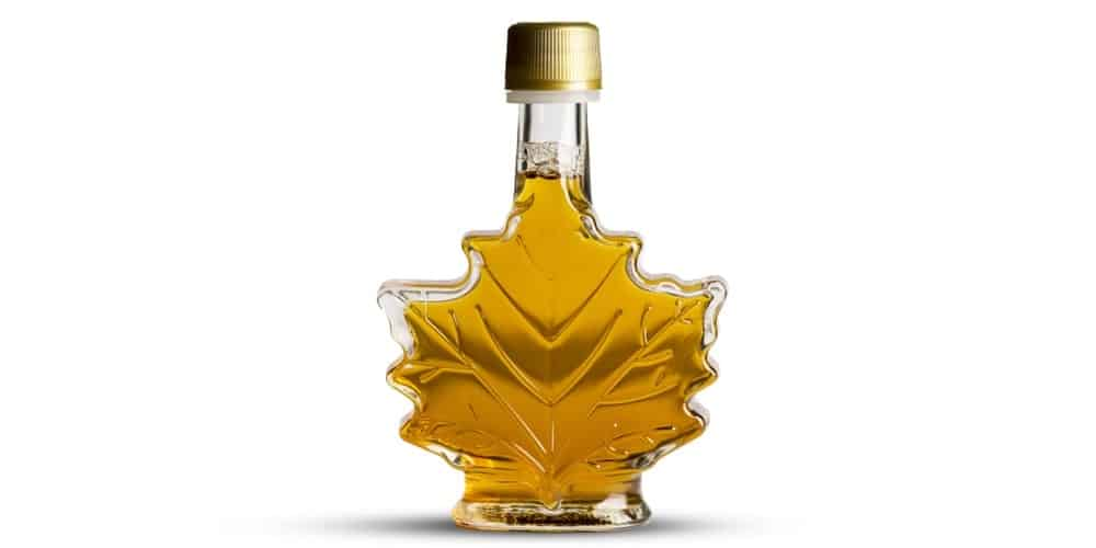 A close look at golden maple syrup in a leaf-shaped bottle.